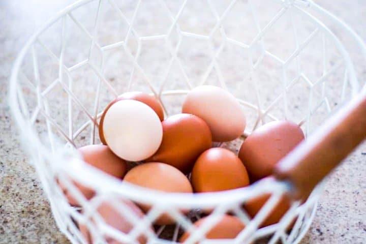 white wire basket full of farm fresh chicken eggs