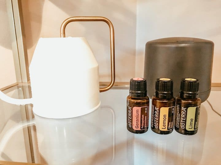 watering can and essential oils on a glass shelf
