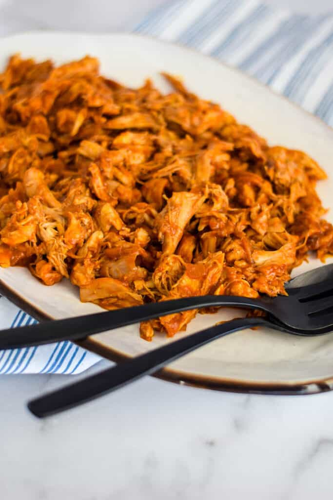 shredded bbq chicken on a white platter with black serving utensils