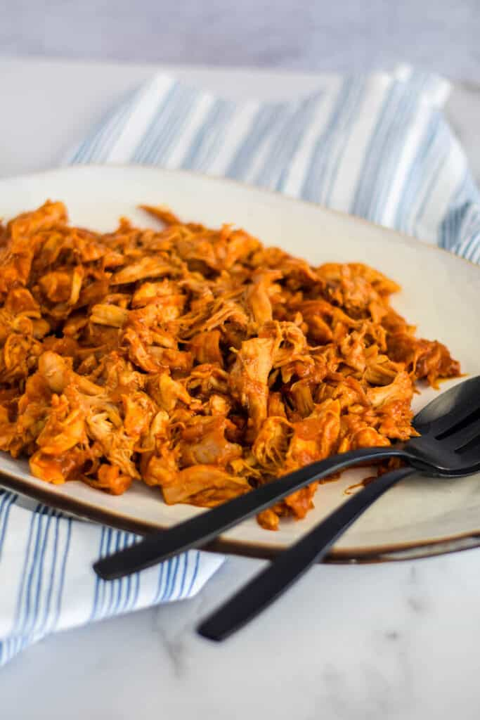 easy shredded chicken with bbq sauce on a white platter with black serving utensils