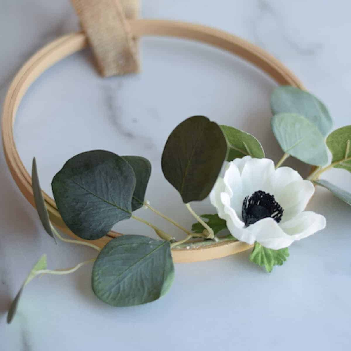 white floral embroidery hoop wreath with eucalyptus leaves