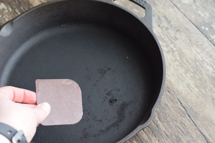 using a plastic scraper to remove burnt on food from cast iron