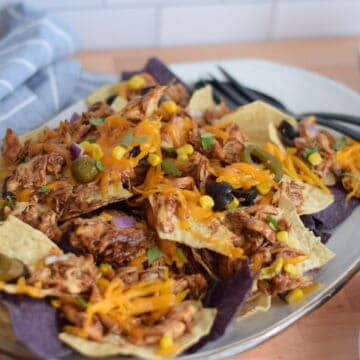 white platter of finished nachos with utensils