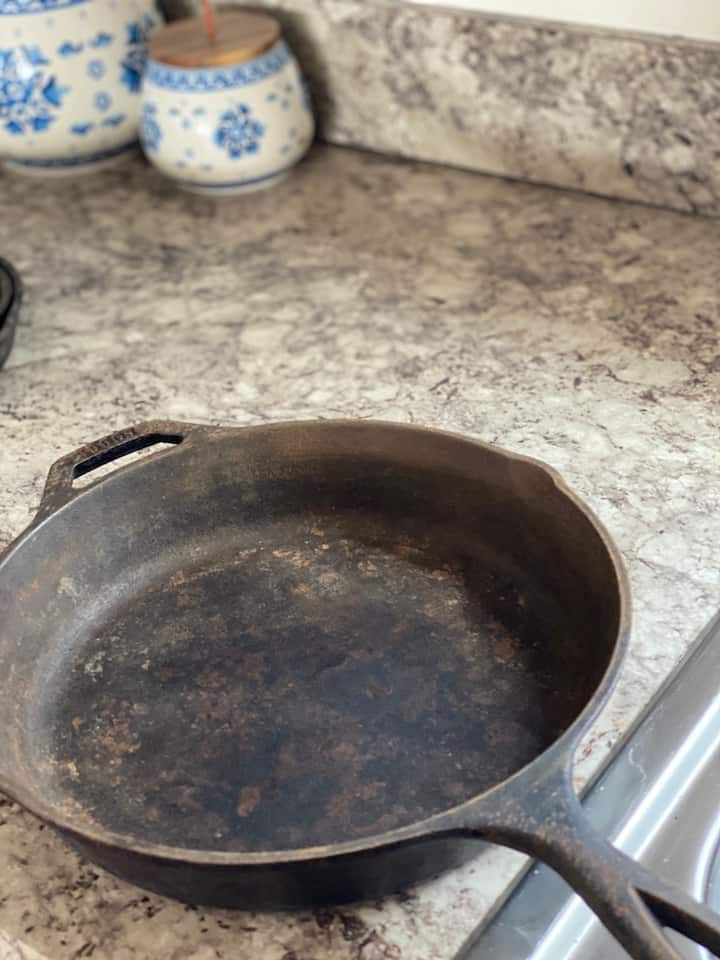 rusty cast iron skillet on a kitchen counter