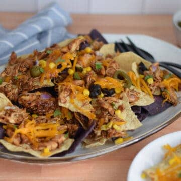 loaded bbq chicken nachos on a white platter with black serving utensils