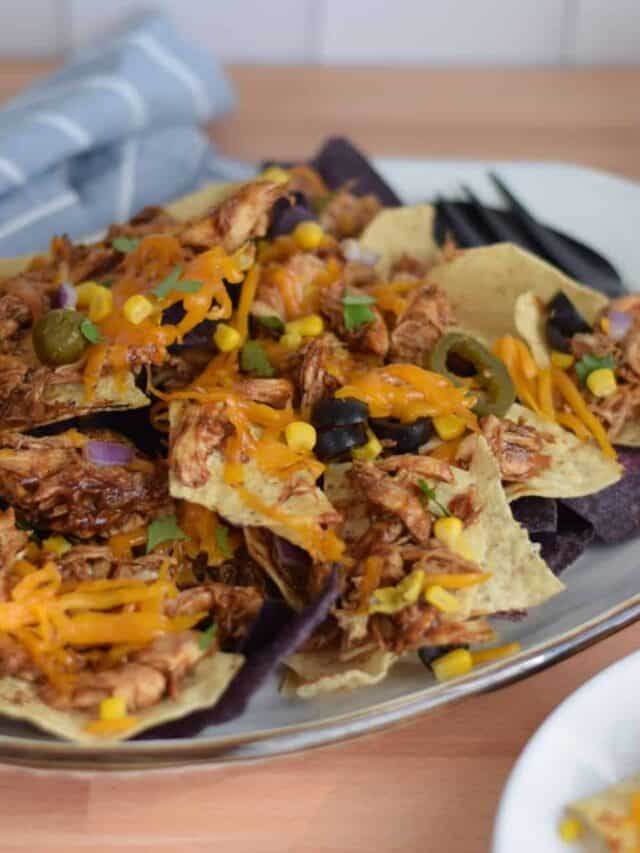 loaded bbq chicken nachos on a white platter with black serving utensils