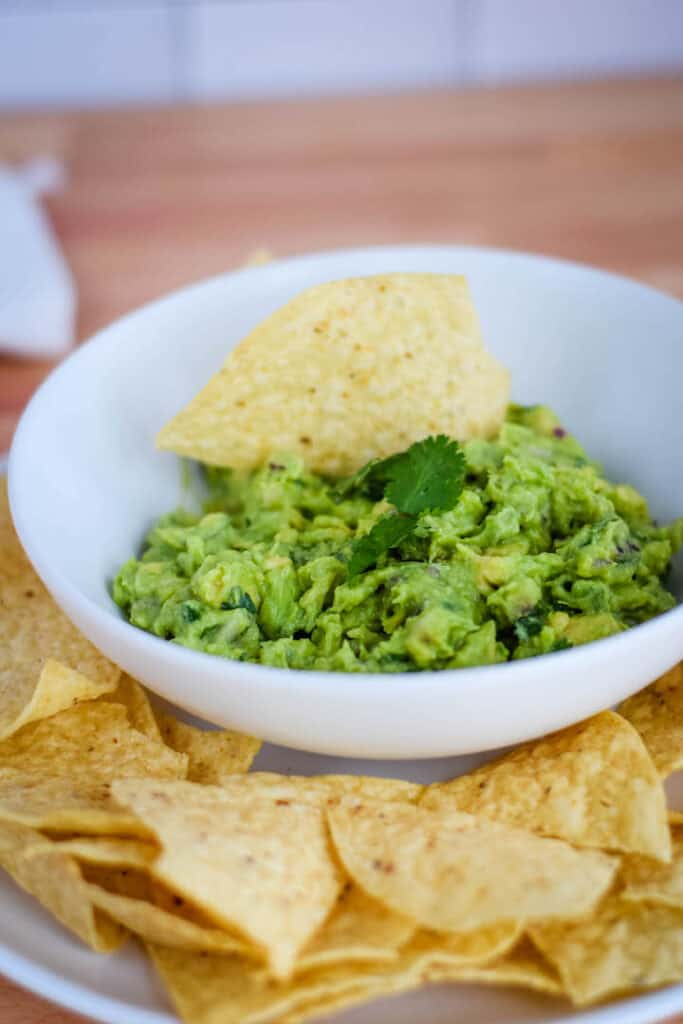 platter of tortilla chips and fresh guacamole with a cilantro garnish