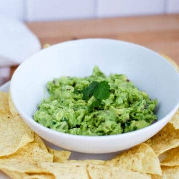 white bowl with homemade guacamole and tortilla chips resting on platter