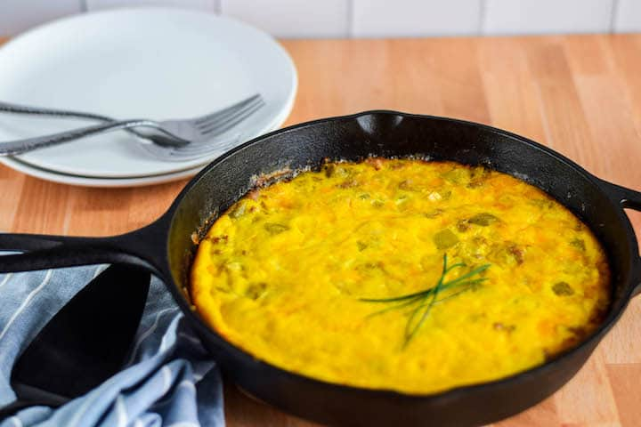 cast iron skillet with smoked frittata and stack of white plates with forks
