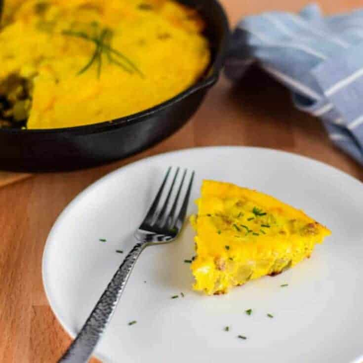 slice of frittata on a white plate with little pieces of garlic chives