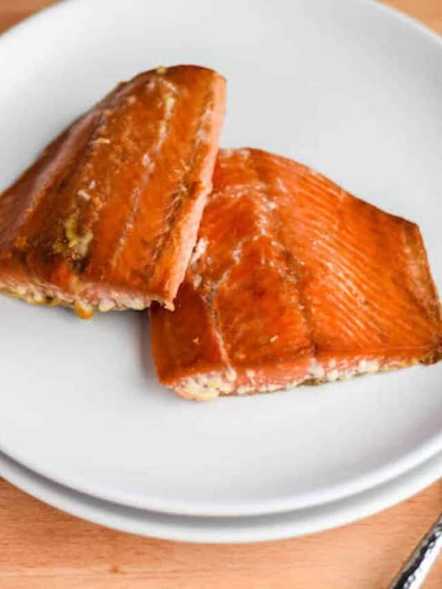 two finished Traeger grilled salmon pieces on a white plate