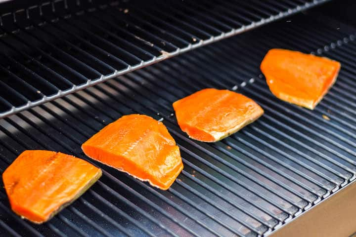 raw salmon pieces being added to the grill