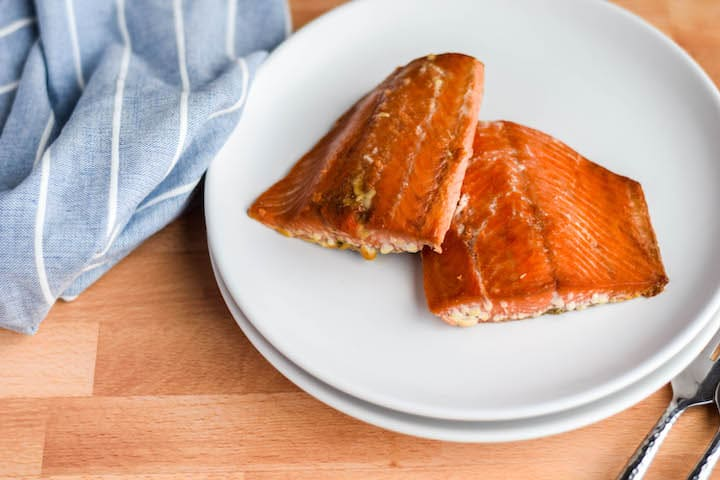 white plates with two grilled salmon pieces