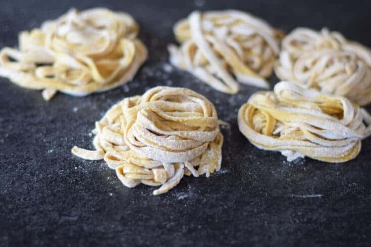 homemade pasta noodles resting into nest piles and drying on black counter top