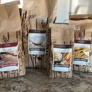 bulk pantry staples of grains and oats in brown paper bags
