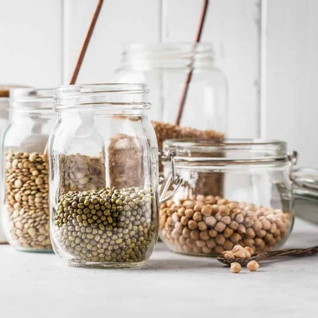 clear mason jars of dried beans on a counter top