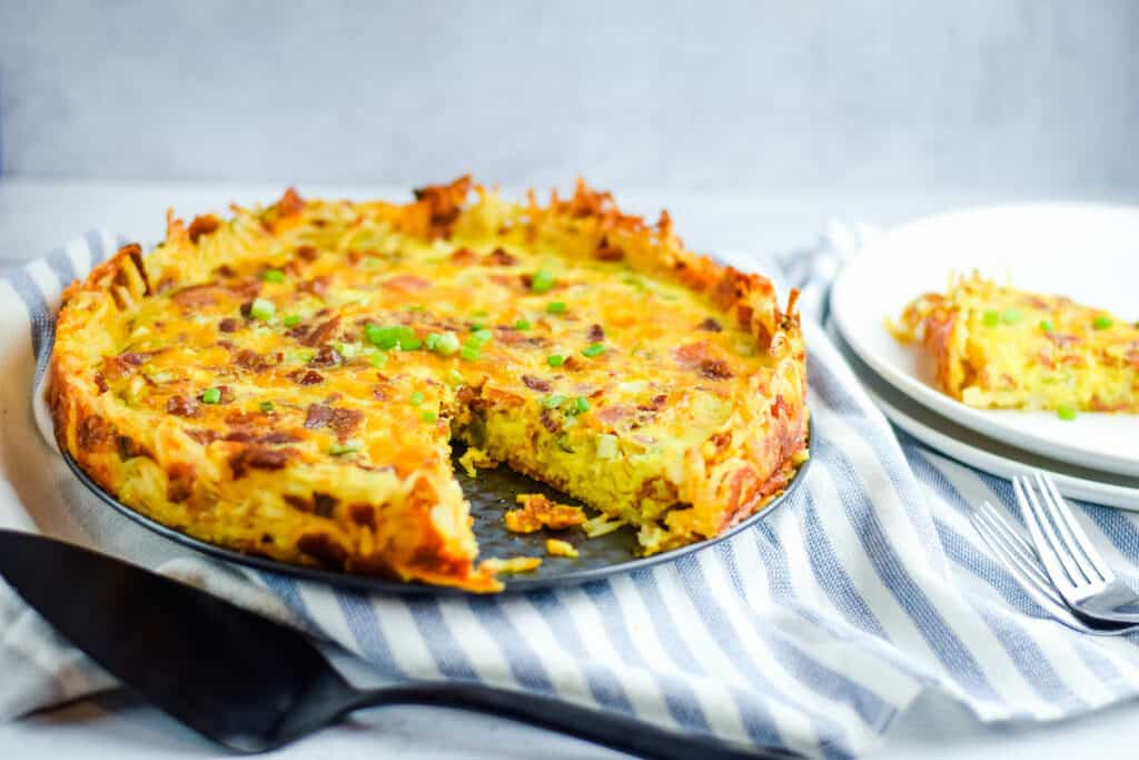 finished hash brown quiche on a dining table with place serving utensils