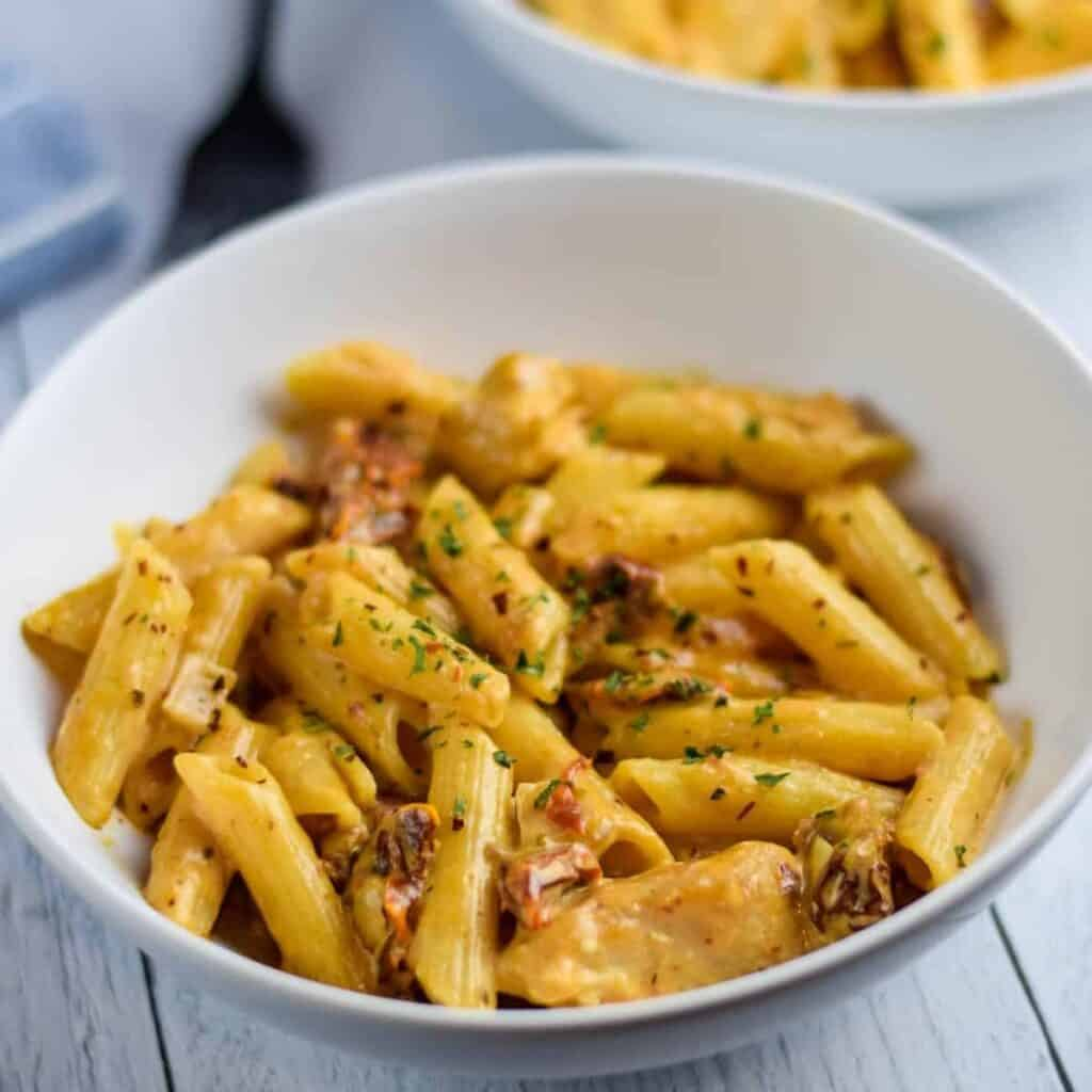close up image of the creamy sun dried tomato pasta in a white bowl on the kitchen table