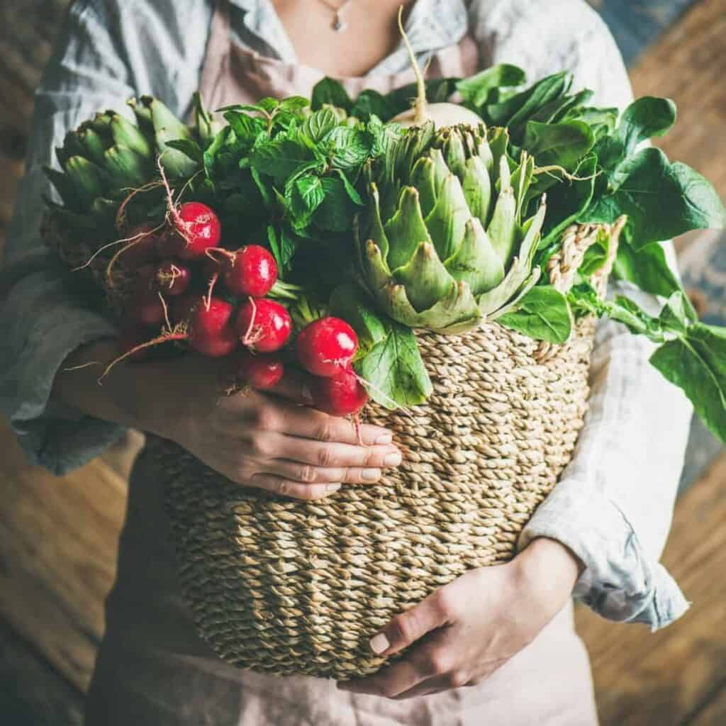 lady carrying basket of fresh harvested vegetables
