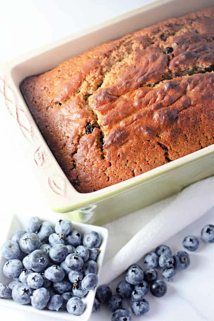 healthy blueberry bread in a loaf pan with a small bowl of  blueberries