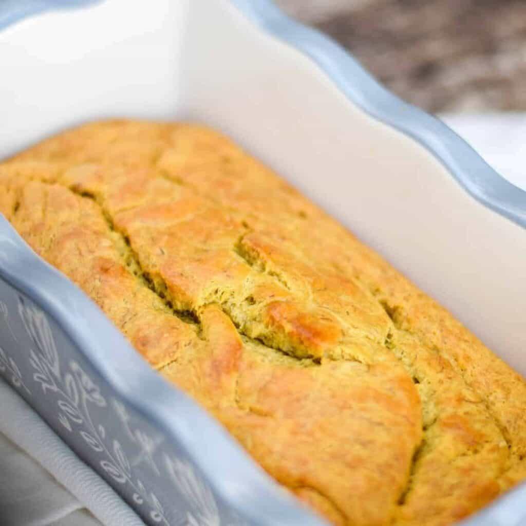 banana bread with honey in a light gray bread pan
