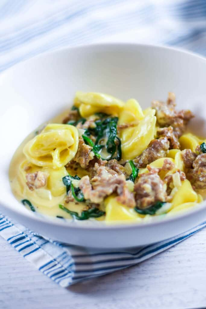 white bowl with finished creamy tortellini