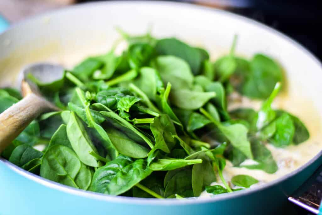 adding the baby spinach to the skillet