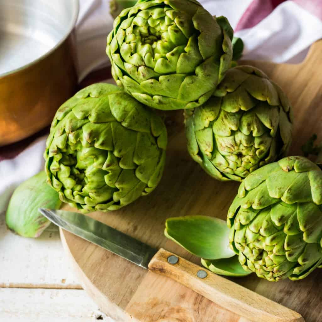 harvested artichokes on a cutting board in the kitchen