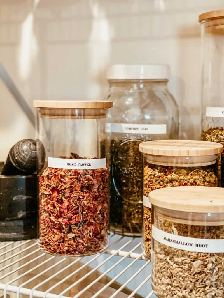 close up of dried herbs and rose petals in storage jars