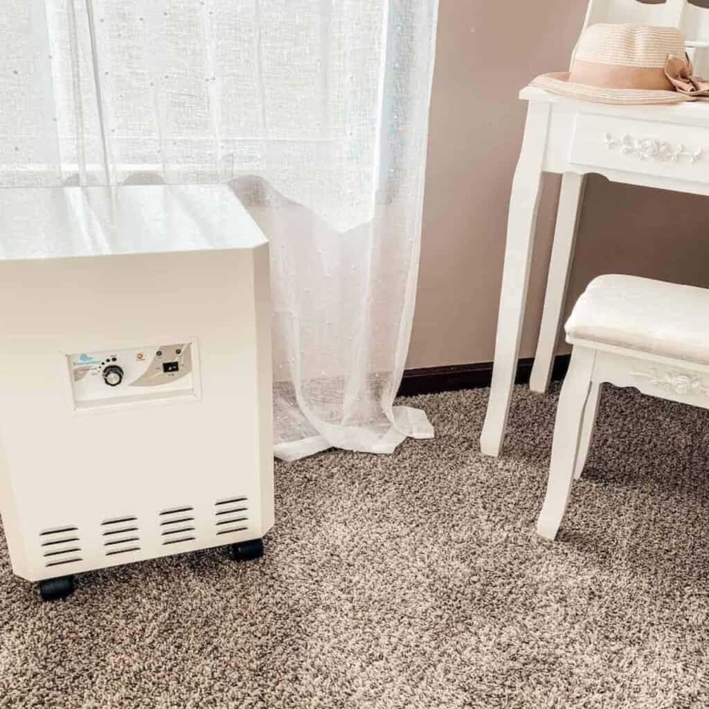 EnviroKlenz Air Purifier in bedroom with sheer white curtains in background