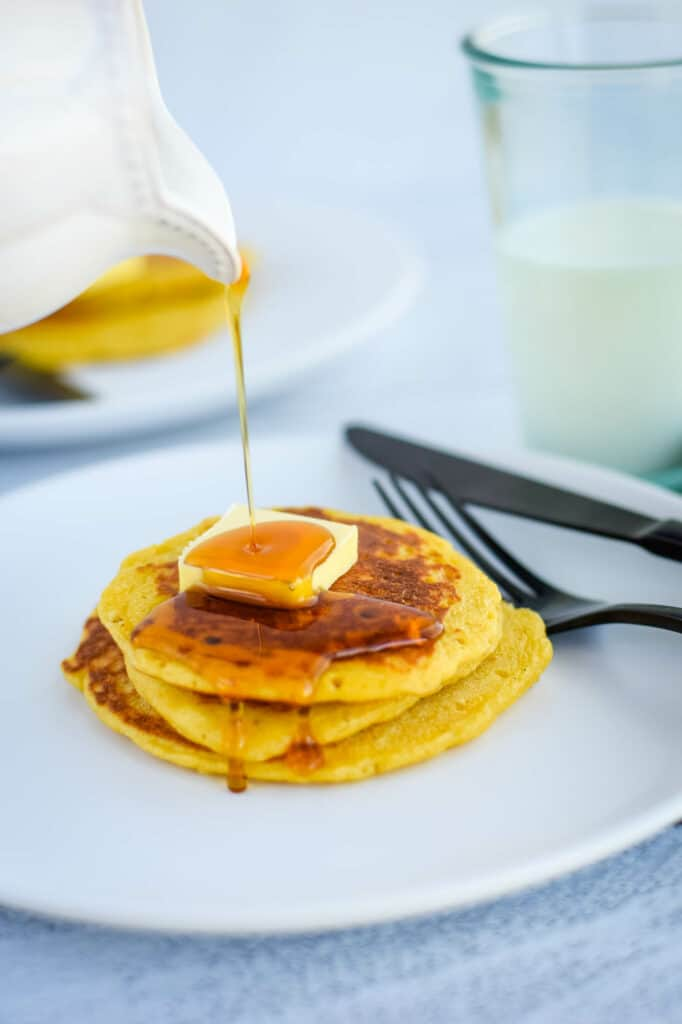 pouring maple syrup over a stack of einkorn sourdough pancakes