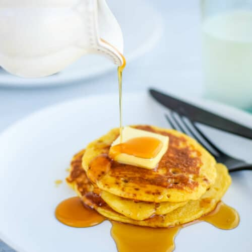 white plate with a stack of fresh pancakes, butter and pouring maple syrup from a small pitcher