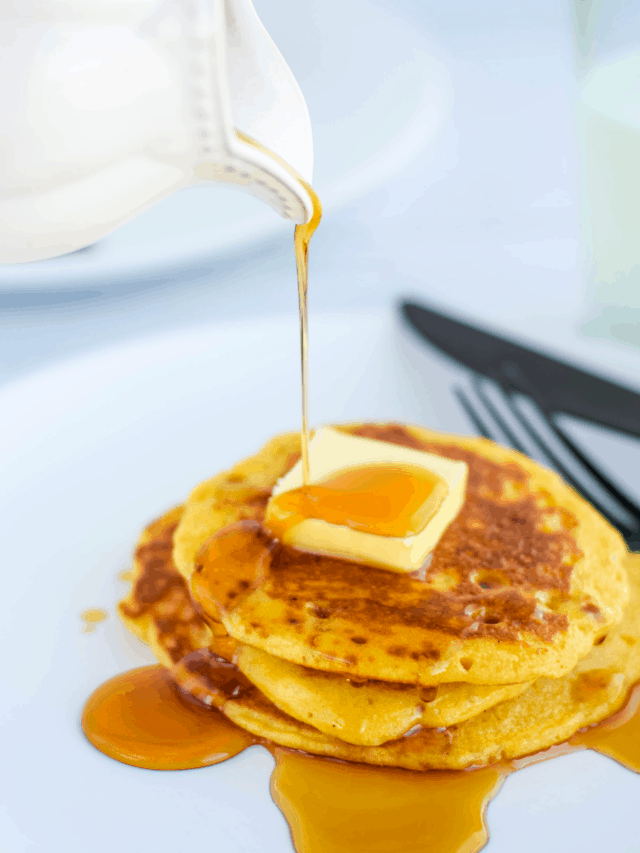 pouring real maple syrup over a stack of cooked einkorn sourdough pancakes