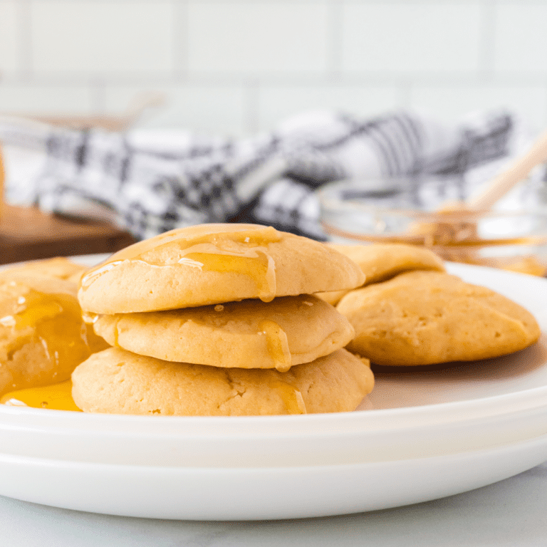honey butter cookies on a white tray with honey in background