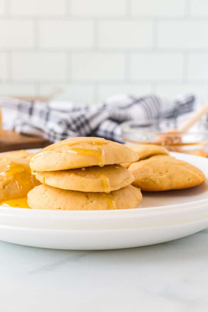 finished honey butter cookies on a white plate with a drizzle of honey